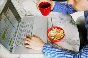 """a man working at home while eating breakfast,"" by EU Social http://www.flickr.com/photos/socialeurope/4303391587/"